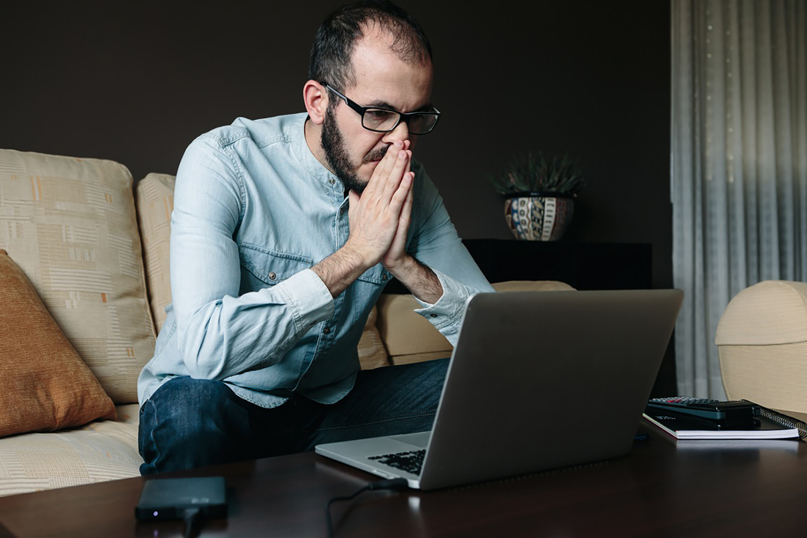 Worried man reading bad news on the laptop computer while working remotely at home. Telecommuting, telework and teleworking concept.